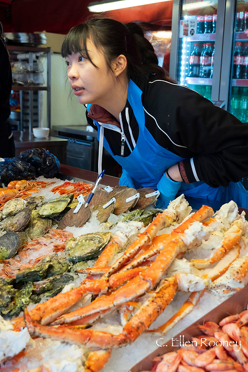 A woman selling shellfish in the fish market in Bergen, Norway