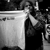 """NORRISTOWN, PA - SEPTEMBER 24:  Becky Haney holds a t-shirt stating """"WE LOVE BILL COSBY,"""" as Bird Milliken protests in the background, after Bill Cosby departed the Montgomery County Courthouse on the first day of sentencing in his sexual assault trial on September 24, 2018 in Norristown, Pennsylvania.  In April, Cosby was found guilty on three counts of aggravated indecent assault for drugging and sexually assaulting Andrea Constand at his suburban Philadelphia home in 2004.  60 women have accused the 80 year old entertainer of sexual assault.  (Photo by Mark Makela/Getty Images)"""