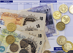File photo dated 15/04/14 of notes and coins on a payslip, as pay deals have remained at 2\% in recent months, with wage freezes at the lowest level for several years, a study shows.