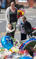 © London News Pictures. 31/05/2013.A woman and her children leave flowers outside Woolwich Barracks in South East London where soldier Lee Rigby was murdered in an attack police are treating as terrorism. The queen had already been scheduled to go to the barracks before her visit was given a new resonance by the attack. Photo credit: Ben Cawthra/LNP