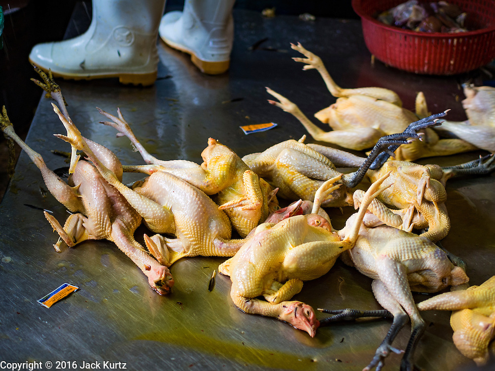 "12 JANUARY 2016 - BANGKOK, THAILAND: Freshly killed chickens ready to be processed in the live poultry section of Khlong Toey Market (also spelled Khlong Toei) in Bangkok. On Monday the Thai Ministry of Public Health instructed government agencies to watch for any signs of ""bird flu"" during the winter season, and warned the public to avoid contact with any birds that appear sickly. The latest data from the World Health Organization showed the continuous transmission of avian flu in various countries, both in people and birds. Bird Flu is endemic in China, Vietnam and Indonesia, all important Thai trading partners. There have been no recorded outbreaks of Bird Flu in humans in Thailand several years.      PHOTO BY JACK KURTZ"