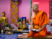 "30 DECEMBER 2017 - BANG KRUAI, NONTHABURI, THAILAND:  A Buddhist monk leads a prayer during a resurrection ceremony at Wat Ta Khien, about 45 minutes from Bangkok in Nonthaburi province. The temple is famous for the ""floating market"" on the canal that runs past the temple and for the ""resurrection ceremonies"" conducted by monks at the temple.      PHOTO BY JACK KURTZ"