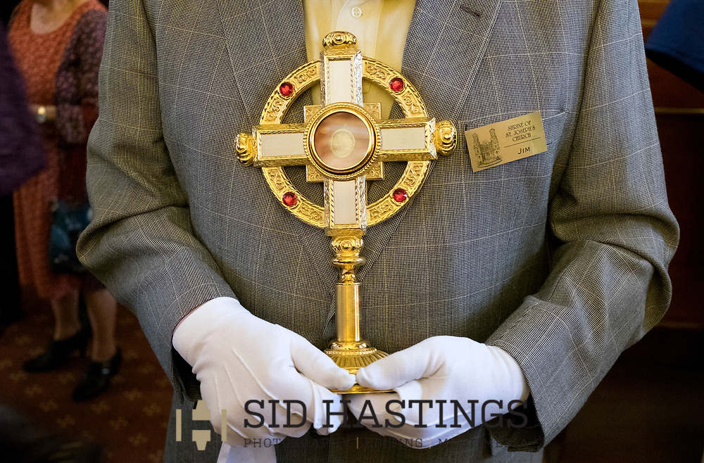 11 MARCH 2018 -- ST. LOUIS -- Shrine of St. Joseph usher Jim Fuller holds a reliquary with a relic of St. Peter Claver after Mass at the Shrine of St. Joseph Sunday, March 11, 2018 in the Columbus Square neighborhood of St. Louis. Strecker descendants gathered to remember the healing of the Strecker, thought mortally ill, during an 1864 service honoring Jesuit priest Peter Claver, a missionary who worked among slaves in South America during the 17th century. Strecker's healing was among the miracles attributed to Claver that led to his 1888 canonization by Pope Leo XIII. Photo © copyright 2018 Sid Hastings.