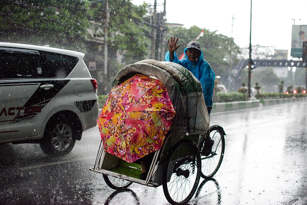 A becak driver and passenger challenge the heavy rainfall in Malang city. <br />