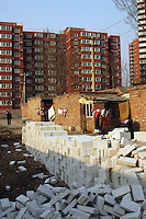 China, Beijing, Ping Fang Xiang, 2008. New materials for temporary walls lie in the narrow strip of land between new construction and traditional housing..