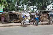 A man loading up his rickshaw with large sacks along a road in Dhaka, Bangladesh.