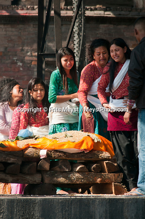 Kathmandu, Central Valley, Nepal, November 2012. A mourning family prepares the body of a deceased family member for a cremation ceremony at the Pashupatinath Temple. Hindus believe that cremation (compared to burial or outside disintegration) is most spiritually beneficial to the departed soul. Pashupatinath Temple is one of the most significant Hindu temples of Lord Shiva in the world, located on the banks of the Bagmati River in the eastern part of Kathmandu. The temple is listed in UNESCO World Heritage Sites list. Photo by Frits Meyst/Adventure4ever.com