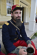 "Old Bethpage, New York, USA. August 30, 2015. ANDREWS PREBLE from Long Beach portrays an American Civil War soldier Captain from the 14th Brooklyn Regiment (14th New York State Militia) AKA The Brooklyn Chasseurs, at the Noon Inn tavern during the Old Time Music Weekend at the Old Bethpage Village Restoration. During their historical reenactments, members of the non-profit 14th Brooklyn Company E wear accurate reproductions of ""The ""Red Legged Devils"" original Union army uniform."