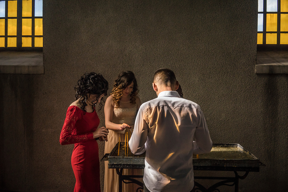 SHUSHI, NAGORNO-KARABAKH - APRIL 18: Guests light candles in prayer before the wedding of groom Davit Simonyan, 24, and bride Shogher Hovsepyan, 25, at Ghazanchetsots church on April 18, 2015 in Shushi, Nagorno-Karabakh. Since signing a ceasefire in a war with Azerbaijan in 1994, Nagorno-Karabakh, officially part of Azerbaijan, has functioned as a self-declared independent republic and de facto part of Armenia, with hostilities along the line of contact between Nagorno-Karabakh and Azerbaijan occasionally flaring up and causing casualties. (Photo by Brendan Hoffman/Getty Images) *** Local Caption ***