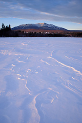 Golden Road near Abol Bridge, ME. Winter. Lines in the snow of a frozen pond lead towards Maine's Mt. Katahdin.