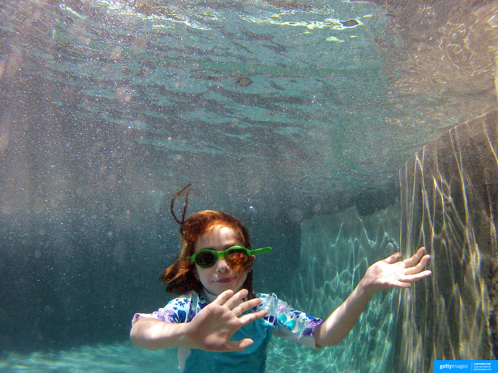 A six year old girl swimming underwater in her back yard family swimming pool. Connecticut, USA. Photo Tim Clayton