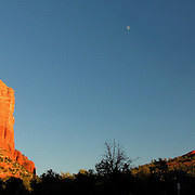 Panoramic of Courthouse and Bell Rocks at sunset, with the moon in between; Sedona, AZ