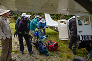 We unload from a small plane at Martins Bay Aerodrome (NZMJ) to start the Hollyford Track in Fiordland National Park, Southland region, South Island of New Zealand. We enjoyed an easy 3-day version of the Hollyford Track: Day 1: fly from Milford Sound to Martins Bay, walk to its oceanfront Hut, and see New Zealand fur seals. Day 2: jetboat on Lake McKerrow to Pyke River Confluence, hike to Hidden Falls Hut for overnight lodging. Day 3: tramp out to Hollyford Road end to our prearranged car shuttle. In 1990, UNESCO honored Te Wahipounamu - South West New Zealand as a World Heritage Area.