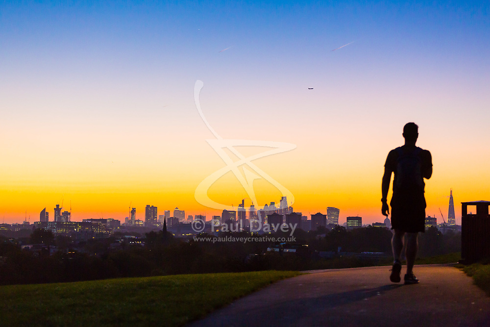 London, October 27 2017. An early morning walker makes a silhouette as the day breaks over London's skyline, seen from Primrose Hill. © Paul Davey