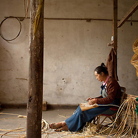 Luo Hongxian prepares rattan for weaving into furniture in the Kangjia Teng Jichang factory in Heshun. The craft of hand-woven rattan furnature was brought to the area from neighboring Myanmar and has been practiced in Heshun for many years. The factory produces everything from chairs to tables to pillows and tissue holders. Most buyers are local but a few have the products shipped across China.