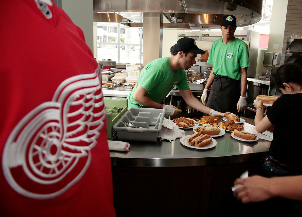 A customer, left, waits in line as cooks and servers prepare orders as the opening of Coney Dog, a Detroit-style Coney Island hot dog restaurant, on Sunset Boulevard in West Hollywood, Calif., Saturday, June 19, 2011. (AP Photo/Jason Redmond)