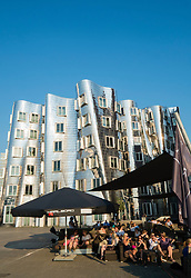 Busy bars in evening at Neuer Zollhof buildings designed by Frank Gehry in Medianhafen in Dusseldorf Germany
