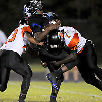 Trask High School's Steven Jordan is tackled by Wallace-Rose Hill High School's Josiah Bryant, left, and Alex Lisane Friday September 26, 2014 in Rocky Point, N.C. (Jason A. Frizzelle)