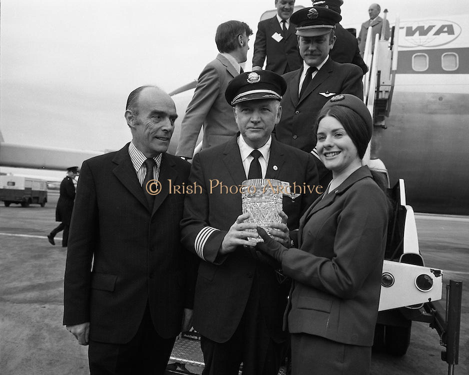First Direct T.W.A.Flight To Dublin.    (G68)..1974..02.05.1974..05.002.1974..2nd May 1974..Today saw the first direct trans-Atlantic flight direct to Dublin airport from the U.S.A. T.W.A. (Trans World Airways) were the flight operators and the aircraft used was a Boeing 707, registry number N799TW..Image  of Miss T Bergin,Carlow, (Aer Rianta) presenting the captain of the first T.W.A.flight direct to Dublin with a crystal vase.Included in the picture is Mr Liam Boyd,Manager in Ireland for T.W.A.