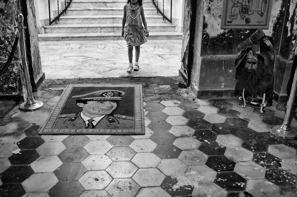 Libye, Benghazi le 09-09-11 El Manar Palace, le  musée de la guerre à Benghazi a ouvert ses portes le 1er août 2011. Situé dans une demeure de style colonial qui date de l'occupation Italienne, face au port, on vient le visiter en famille chaque jour entre 17 heures et minuit. Lors de sa récente visite en Libye, le président français Nicolas Sarkozy s'y est rendu encompagnie de James Cameron et du chef du CNT. À l'entrée, on peut y apercevoir une statue en carton pâte du colonel Mouammar Kadhafi derrière des barreaux. Au rez de chaussée, l'artiste libyen Ali Al Wakwak expose ses oeuvres, des sculptures faites de balles, de mortiers et de caisses de munitions récupérés sur le champ de bataille du côté de Brega et Ras Lanouf. À l'étage c'est un collectif d'artistes locaux qui exposent des caricatures du dictateur aujourd'hui en fuite. Des encres, des pyrogravures mais aussi des escquisses de dessin. Ce genre de caricatures ornent déjà le centre de presse et les rues de Benghazi depuis les premières heures de la révolution. Devant le grand escalier, la direction a pris le soin de conserver un tapis à l'éffigie de Kadhafi sur lequel chaque visiteur prend un malin plaisir à s'essuyer les pieds. Ce musée a pour vocation de donner accès à l'art, une chose qui n'existait pas sous l'ère de Kadhafi.