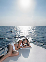 Young woman in bikini relaxing on yacht