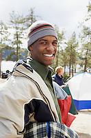 Young man at campsite portrait half length