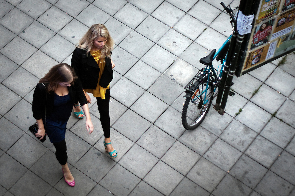 Two girls are walking at the streets of Stockholm.