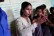 Bhawani Regmi (grey/pink), 16, speaks of a child marriage incident she previously witnessed, at a club meeting at the Kishuri Sachetana Child Club in their activity center in Thahuri Tole, Chhinchu, Surkhet district, Western Nepal, on 1st July 2012. Bhawani's ambition is to be a doctor. 16-year-old Bhawani Regmi (in grey/pink) who is the president of the district level child forum, 11-year-old  Sarawati Regmi (in white), and 10-year-old Ganga Regmi (in pink) are daughters of pandit (Hindu priest) Dharma Raj Regmi who is one of the 3 priests who have agreed to stop solemnizing child marriages. These Child Clubs, supported by the government, Save the Children and their local partner NGO Safer Society, advocate for child rights and against child marriages and use peer support and education to end child marriages and raise awareness. Photo by Suzanne Lee for Save The Children UK