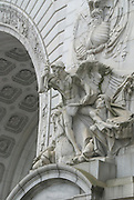"""On the south side of the arch of the Manhattan Bridge, on the Manhattan side, lies """"The Spirit of Commerce,"""" a large sculptural panel designed by Carl Augustus Heber. The soffit of the arch is covered with deeply cut rosettes."""