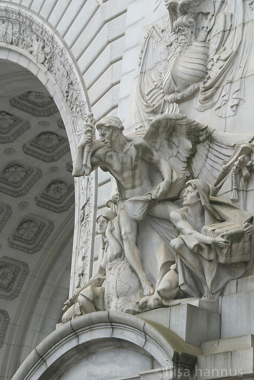 "On the south side of the arch of the Manhattan Bridge, on the Manhattan side, lies ""The Spirit of Commerce,"" a large sculptural panel designed by Carl Augustus Heber. The soffit of the arch is covered with deeply cut rosettes."