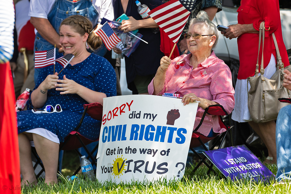 """Woman with a Covid-19 denail sign at a """"Save America Rally"""" in Baton Rouge on the 4th of July across the street from the Governor's Mansion where about 200 gathered. The 4th of July rally was organized by Jeff Crouer, Mimi Owens and Woody Jenkins, chairman of the executive committee for the Republican Party in East Baton Rouge Parish. Rev. Tony Spell of Life Tabernacle Church who has held church services in defiance of a stay-at-home order throughout the pandemic was one of the speakers. He an other speakers expressed their displeasure of being told to wear a mask to prevent the spread of Covid-19 and the removal of confederate monuments."""