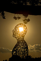 Stock photo of Artist Jaume Plensa's Tolerance sculptures on Allen Parkway in Houston Texas at sunset