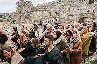 """MATERA, ITALY - 5 OCTOBER 2019: A scene of the Via Crucis, with the crowd following and pushing Jesus Christ on his way to crucifixion, is seen here during the production of """"The New Gospel"""", a film by Swiss theatre director Milo Rau, in Matera, Italy, on October 5th 2019.<br /> <br /> Theatre Director Milo Rau filmed the Passion of the Christ  under the title """"The New Gospel"""" with a cast of refugees, activists and former actors from Pasolini and Mel Gibson's films.<br /> <br /> The role of Jesus is performed by Yvan Sagnet, a Political activist born in Cameroon and who worked on a tomato farm when in 2011 he revolted against the system of exploitation and led the first farm workers' strike in southern Italy. In a series of public shoots in the European Capital of Culture Matera, Jesus will proclaimed the Word of God, was crucified (October 6th 2019) and finally rose from the dead in Rome, the capital of Catholic Christianity and seat of one of the most xenophobic governments in Europe (October 10th 2019).<br />  <br /> Parallel to the film, the humanistic message of the New Testament was transformed into the present: at the beginning of September, the campaign """"Rivolta della Dignità"""" (Revolt of Dignity), which demanded fair working and living conditions     for refugees, global freedom of travel and civil rights for all, started with a march from the southern Italian refugee camps. """"It's about putting Jesus on his feet,"""" director Milo Rau said. Led by Jesus actor Yvan Sagnet, the campaign fights for the rights of migrants who came to Europe via the Mediterranean to be enslaved by the Mafia in the tomato fields of southern Italy and to live in ghettos under inhumane conditions. The campaign and the film thus create a """"New Gospel"""" for the 21st century, a manifesto of solidarity with the poorest, a revolt for a more just and humane world."""