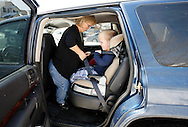 Barb Kotzian (L) can stand upright in her car as she buckles son Adam into his car seat outside their home in Thornton, Colorado March 25, 2010.  Barb and Adam are both achondroplasia dwarfs, a rare genetic disorder of bone growth.  Preferring to be called little persons Barb is active in the Little People of America, the only dwarfism support organization that includes all 200+ forms of dwarfism.  REUTERS/Rick Wilking (UNITED STATES)
