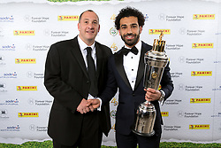 Liverpool's Mohamed Salah and sponsor pose with the PFA Player Of The Year Award Trophy during the 2018 PFA Awards at the Grosvenor House Hotel, London
