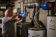 Mike Lehman from the Coporation for Appalachian Development (COAD) prepares test holes before a hot water tank inspection at 47 West Washington Street on Tuesday, June 23, 2015. The inspection was part of a whole house energy audit.  Photo by Ohio University  /  Rob Hardin