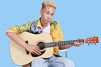 Portrait of a young teenage boy playing guitar over blue background
