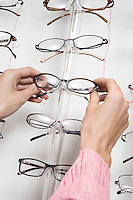 Woman choosing eyeglasses from rack
