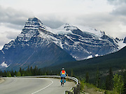 A bicyclist rides the Icefields Parkway beneath glaciers hanging from 12,000-foot peaks in Banff National Park, Alberta, Canada. This is part of the Canadian Rocky Mountain Parks World Heritage Site declared by UNESCO in 1984.
