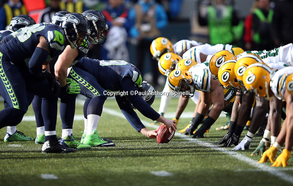 The Seattle Seahawks offensive line gets set to snap the ball at the line of scrimmage opposite the Green Bay Packers defensive line during the NFL week 20 NFC Championship football game against the Green Bay Packers on Sunday, Jan. 18, 2015 in Seattle. The Seahawks won the game 28-22 in overtime. ©Paul Anthony Spinelli