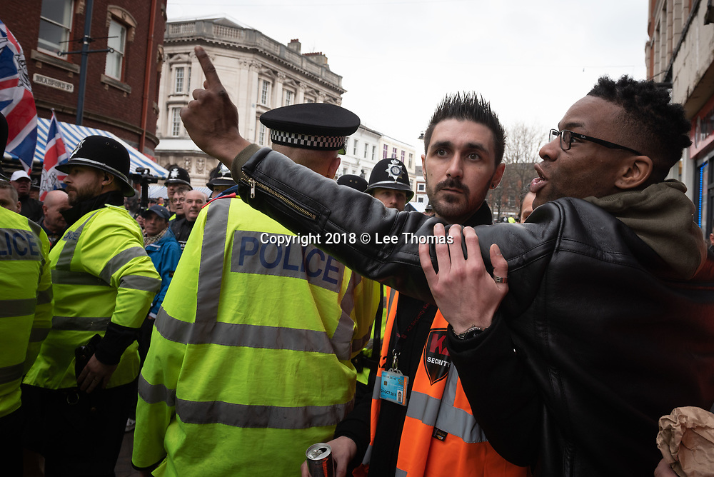 Walsall, West Midlands, UK. 7th April 2018. Pictured:  Locals chant back as EDL supporters march through the town centre. / Up to 60 English Defence League supporters take to the streets of Walsall to protest against their claims that the West Midlands town has problems with child exploitation and no-go areas. Scores of police formed a barrier between English Defence League supporters and a vocal anti-fascist contingent, individual protests of which took place only yards away from each other. // Lee Thomas, Tel. 07784142973. Email: leepthomas@gmail.com  www.leept.co.uk (0000635435)