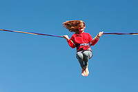 "Brighton, England - child having fun on a giant elastic cord ""ride"" on Brighton beach - Photograph by Owen Franken"
