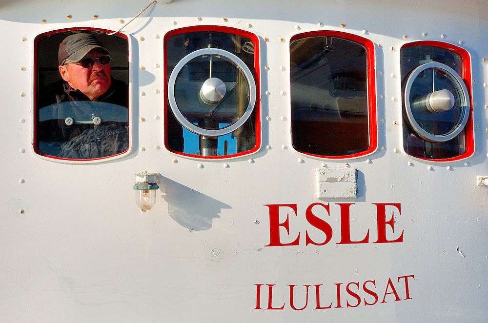 """Fisherman on his ship, scene of everyday day in Ilulissat, the third largest settlement in Greenland with population 4533. Greenland (Greenlandic: Kalaallit Nunaat, meaning """"Land of the Kalaallit (Greenlanders) is a self-governing Danish province located between the Arctic and Atlantic Ocean. A recent study by researchers from NASA's Goddard Space Flight Center shows that Greenland's ice sheet, about 8% of the Earth's grounded ice, is losing ice mass."""