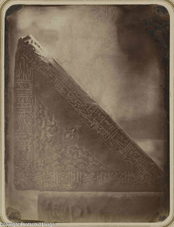 1868<br /> This photograph of a posterior triangular side of the marble Qur'an holder at the main mosque of the Bibi Khanym ensemble in Samarkand (Uzbekistan) is from the archeological part of Turkestan Album. The six-volume photographic survey was produced in 1871-72 under the patronage of General Konstantin P. von Kaufman, the first governor-general (1867-82) of Turkestan, as the Russian Empire&rsquo;s Central Asian territories were called. The album devotes special attention to Samarkand&rsquo;s Islamic architecture, such as 14th- and 15th-century monuments from the reign of Timur (Tamerlane) and his successors. Built in 1399-1405 with the spoils of Timur&rsquo;s campaign in India, the Bibi Khanym ensemble was the location of the city&rsquo;s main, or Friday, mosque, named in homage to Timur&rsquo;s senior wife, Sarai Mulk Khanym. The ensemble centers on the mosque, one of the largest in the Islamic world. Inside the mosque was an enormous Qur'an holder (rihal) donated by Timur&rsquo;s grandson Ulugh Beg and consisting of two massive triangular marble blocks resting on a marble plinth. Shown here is the posterior triangular side of the right block, with carved decoration consisting of floral patterns and bands of cursive script. (Background detail was reduced to highlight the carving.) In 1875, a few years after this photograph was taken, the lectern was moved into the courtyard in front of the mosque.