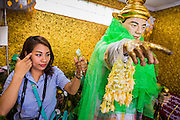 04 JUNE 2014 - YANGON, YANGON REGION, MYANMAR: A woman wraps a deity to make merit for good luck in Botataung Paya (Pagoda) in Yangon, Myanmar (Rangoon, Burma). Botataung is one of the most famous pagodas in Yangon with maze like interior of gold leaf covered walls. The pagoda houses a hair from the Buddha and is one of the most sacred sites in Burma. Yangon, with a population of over five million, continues to be the country's largest city and the most important commercial center.     PHOTO BY JACK KURTZ