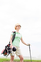 Low angle view of smiling female golfer standing against clear sky