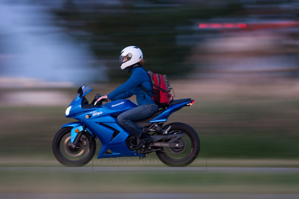 A woman dressed in all blue rides her Kowasaki Motorcycle