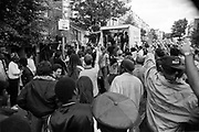 A mobile sound system in a lorry surrounded by a large crowd of people punching their fists in the air, Notting Hill Carnival, London, 1989