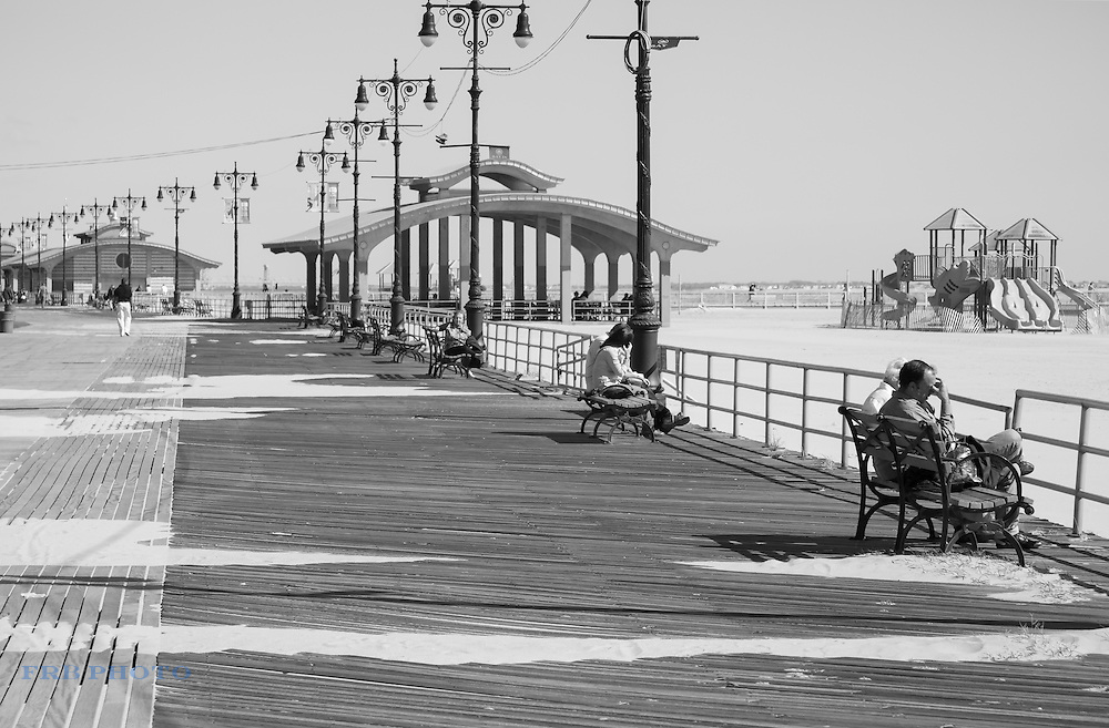 People sitting on benches on Boardwalk at Coney Island in Brooklyn, New York.
