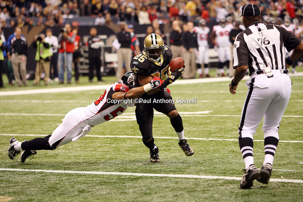 NEW ORLEANS - DECEMBER 07: Running back Reggie Bush #25 of the New Orleans Saints catches a touchdown pass good for a 7-0 lead while avoiding a tackle by linebacker Michael Boley #59 of the Atlanta Falcons at the Louisiana Superdome on December 7, 2008 in New Orleans, Louisiana. The Saints defeated the Falcons 29-25. ©Paul Anthony Spinelli *** Local Caption *** Reggie Bush;Michael Boley